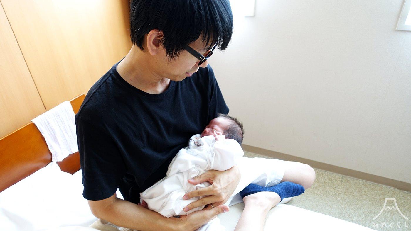 赤ちゃんを抱っこしているトモヒコ